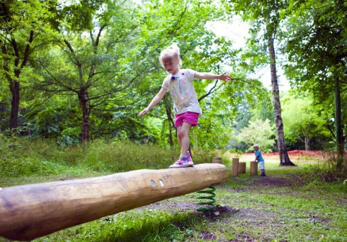 Young girl playing on one of the balance beams